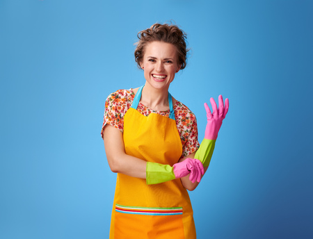 Big cleaning time. happy young housewife pulling on rubber glove isolated on blue background