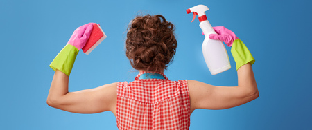 Big cleaning time. Seen from behind modern woman in a yellow apron with kitchen sponge and a bottle of detergent showing biceps isolated on blue