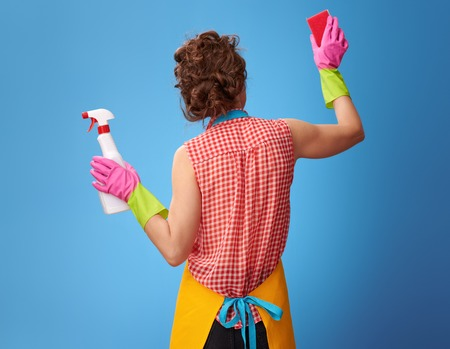 Big cleaning time. Seen from behind young woman in a yellow apron with cleaning detergent using kitchen sponge isolated on blue Stock Photo