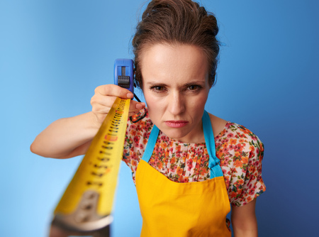 Big cleaning time. modern woman in a yellow apron measuring with tape measure against blue background