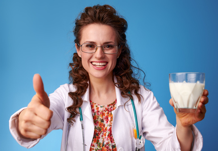 smiling paediatrist doctor in white medical robe showing thumbs up and giving a glass of milk against blue background