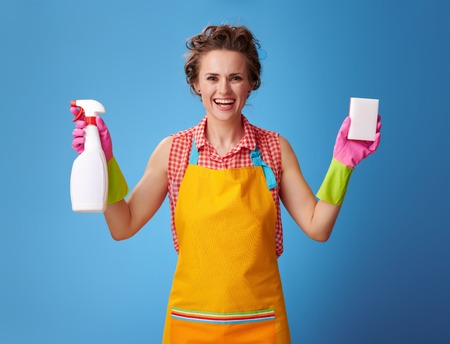 Big cleaning time. smiling young housewife in a yellow apron showing cleaning sponge and detergent isolated on blue background Stock fotó