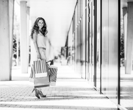 A brown-haired woman stops for a moment to look back a the viewer. She is clearly happy about her many purchases, all held in colourful shopping bags with patterns that contrast with the muted, gentle background colours. The doors lead into an exclusive shopping mall.