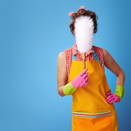 Big cleaning time. young woman in a yellow apron with a duster brush in the front of face isolated on blue