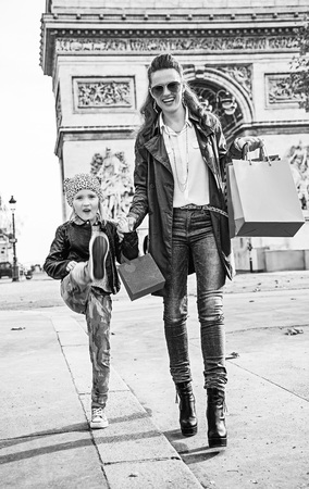 Stylish autumn in Paris. Full length portrait of happy trendy mother and child with shopping bags near Arc de Triomphe in Paris, France going forward