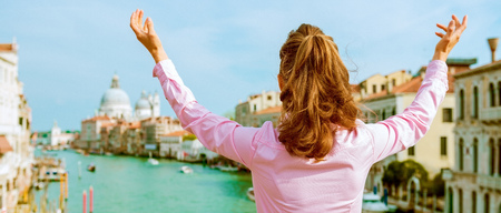 Happy young woman standing on bridge with grand canal view in venice, italy