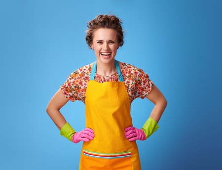 Big cleaning time. Portrait of smiling modern housewife with rubber gloves isolated on blue background