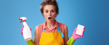 Big cleaning time. shocked modern woman in a yellow apron with kitchen sponge and a bottle of detergent isolated on blue background