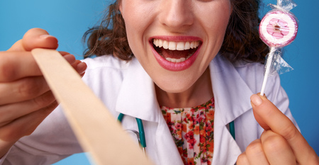 happy paediatrist doctor in white medical robe with lollipop using a spatula to examine throat isolated on blue Stock Photo
