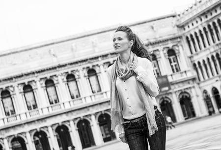 Happy young woman walking on piazza san marco in venice, italy