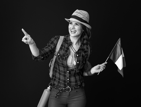 Searching for inspiring places. happy active woman hiker in a plaid shirt with the flag of Italy pointing at something against background