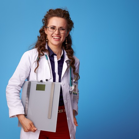 happy medical doctor woman in white medical robe with scales isolated on blue