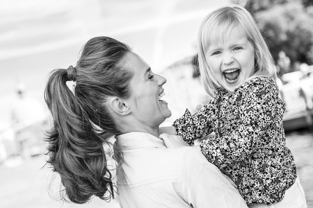 Discovering new places together is just the best, isn't it? Here, a mother lovingly holds her daughter, laughing at how silly and happy her daughter is being while she holds her in her arms. Stockfoto - 102064950