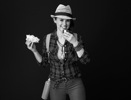 Searching for inspiring places. happy young traveller woman in a plaid shirt having meal break against background Stock Photo