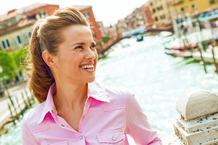 A pretty brunette tourist leans casually against a bridge over one of Venices canals, smiling and looking into the distance. She is relaxed and happy. 版權商用圖片