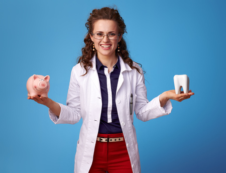 smiling medical doctor woman in white medical robe showing a tooth and piggy bank isolated on blue 스톡 콘텐츠