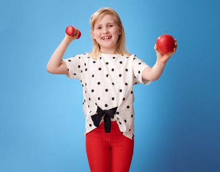 smiling modern girl in red pants showing biceps and an apple isolated on blue
