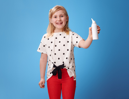 smiling modern girl in red pants isotonic seawater nasal spray on blue background