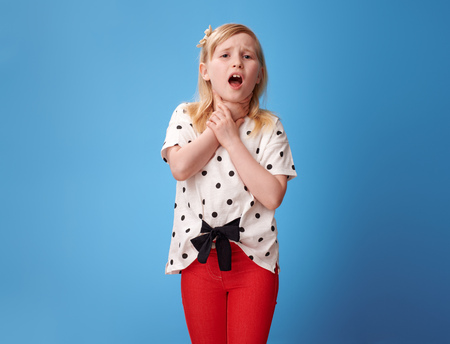 modern child in red pants with neck pain isolated on blue background