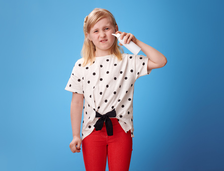 unhappy modern girl in red pants using isotonic seawater nasal spray on blue background 스톡 콘텐츠 - 102285047