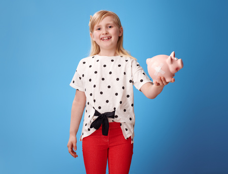 happy modern child in red pants showing piggy bank with plaster isolated on blue background