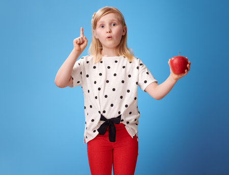 modern girl in red pants with an apple got idea on blue background