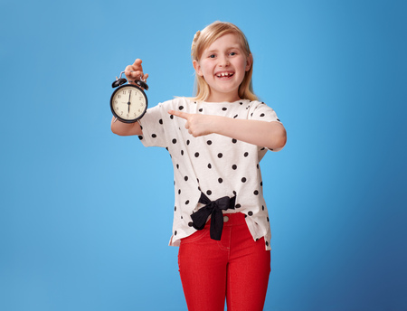 happy modern child in red pants poiting at alarm clock on blue background