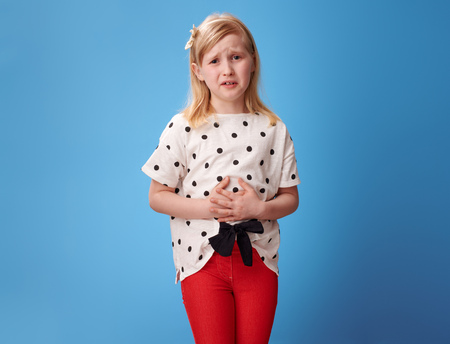 sad modern child in red pants with abdominal pain against blue background Reklamní fotografie