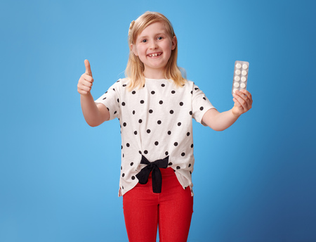 happy modern child in red pants showing thumbs up and and pill isolated on blue background 版權商用圖片