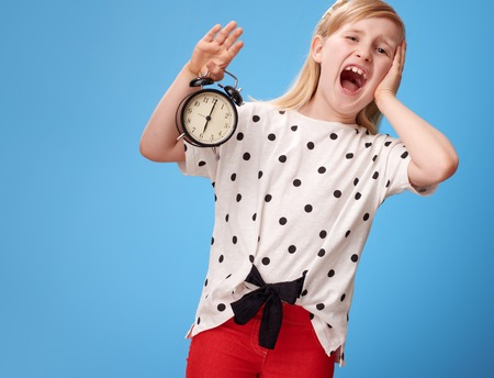 stressed modern child in red pants with alarm clock isolated on blue Stock Photo