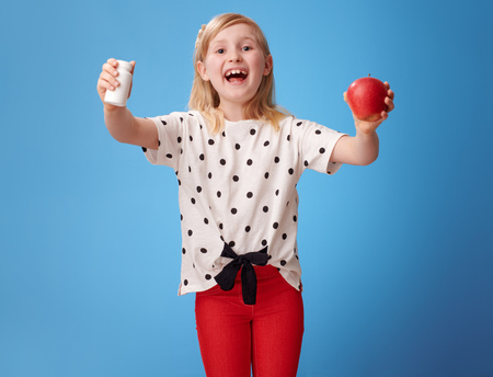 smiling modern child in red pants showing an apple and bottles of vitamins against blue background