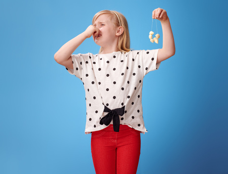 smiling modern child in red pants showing garlic beads and closing nose isolated on blue Stock Photo