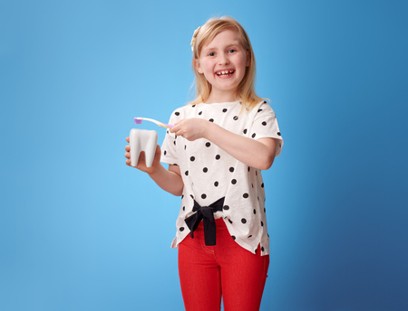 happy modern girl in red pants brushing tooth with toothbrush against blue background