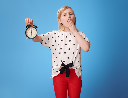 modern child in red pants showing alarm clock and yawing isolated on blue background