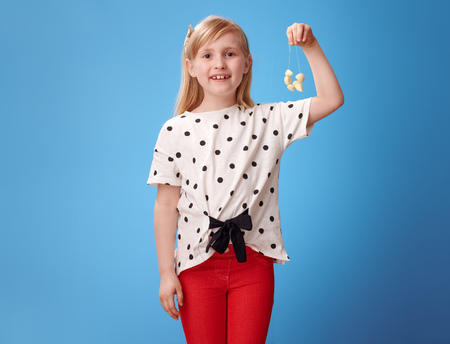 smiling modern girl in red pants showing garlic beads isolated on blue