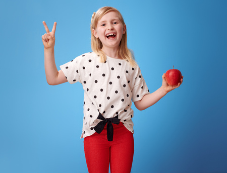 happy modern child in red pants with an apple showing victory gesture on blue background