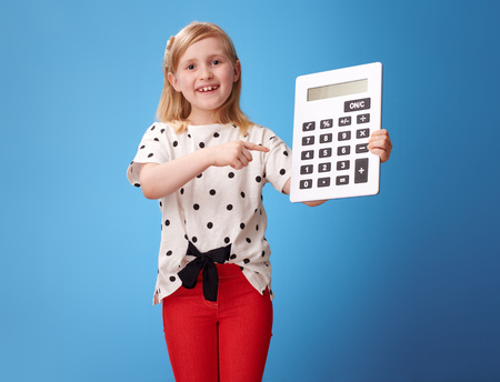 happy modern child in red pants pointing at calculator isolated on blue 스톡 콘텐츠