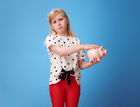 sympathetic modern girl in red pants fondle piggy bank with plaster against blue background