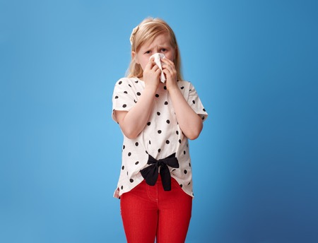 unhappy modern child in red pants blowing nose on blue background Stock Photo