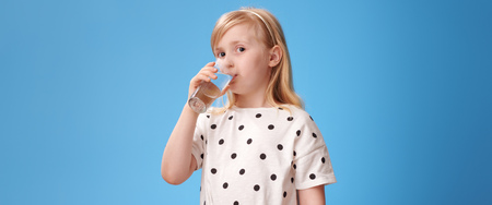 modern child in red pants drinking glass of water on blue background Foto de archivo