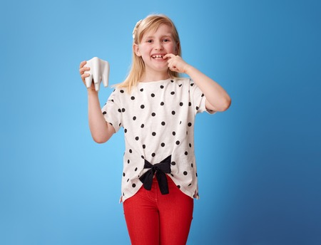 happy modern child in red pants showing tooth against blue background