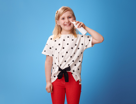 smiling modern girl in red pants using isotonic seawater nasal spray against blue background