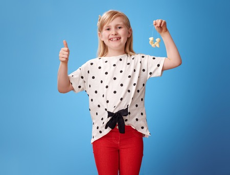 happy modern child in red pants showing thumbs up and garlic beads isolated on blue