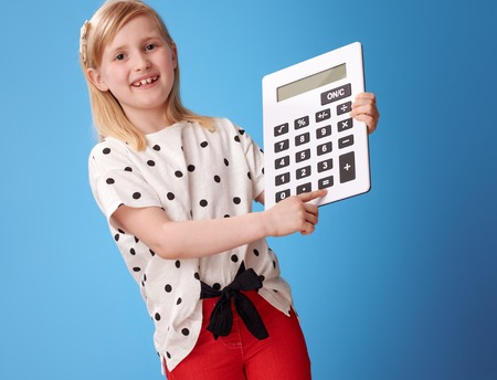 happy modern child in red pants сlicking on the button on the calculator on blue background