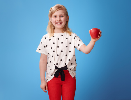 smiling modern girl in red pants showing an apple on blue background 版權商用圖片