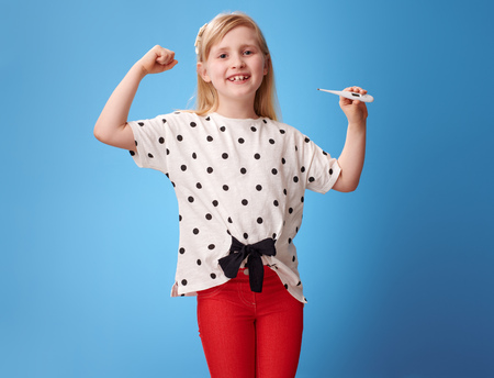 happy modern girl in red pants showing biceps and thermometer on blue background