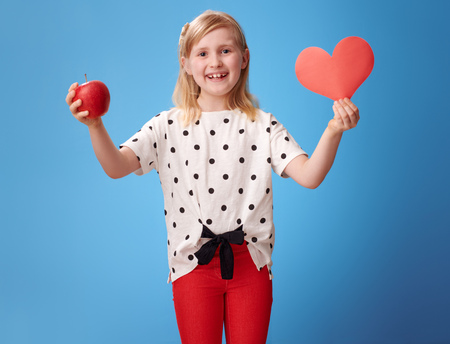 smiling modern child in red pants showing a paper heart and an apple on blue background