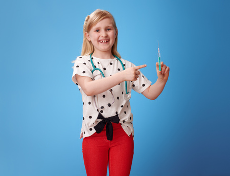 smiling modern child in red pants with a stethoscope pointing at syringe against blue background Stock Photo