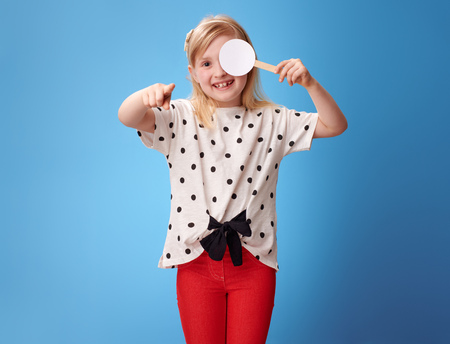 smiling modern girl in red pants with covered one eye taking the visual acuity test and pointing in camera isolated on blue background