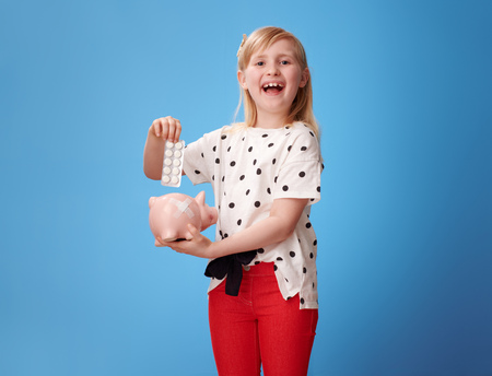 smiling modern child in red pants putting blister pack of pills into piggy bank with plaster on blue background